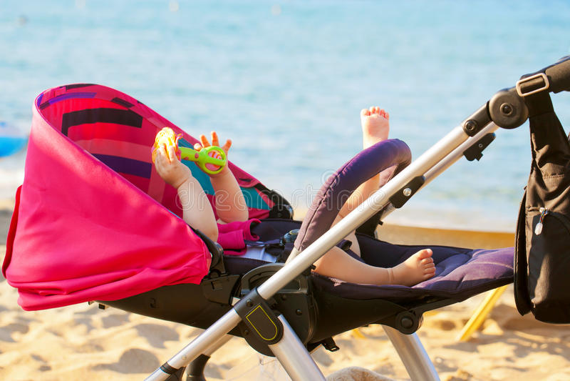 Bebé que miente en cochecito en la playa fotos de archivo