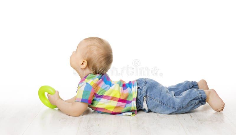 Bebé que miente en el piso blanco, vista posterior trasera del niño que mira lejos imagen de archivo libre de regalías