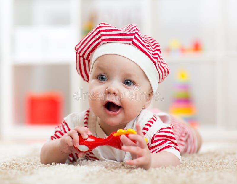 Bebé que miente en el piso y los juegos con el juguete interior fotografía de archivo