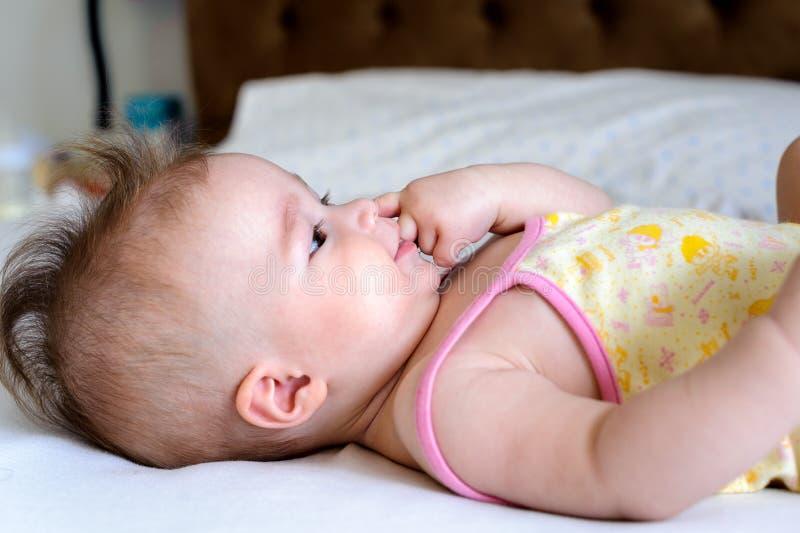 Bebé que miente en la hoja y el finger blancos en su boca foto de archivo libre de regalías