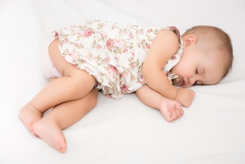 Bebé que miente en una cama mientras que duerme en un cuarto brillante fotos de archivo libres de regalías