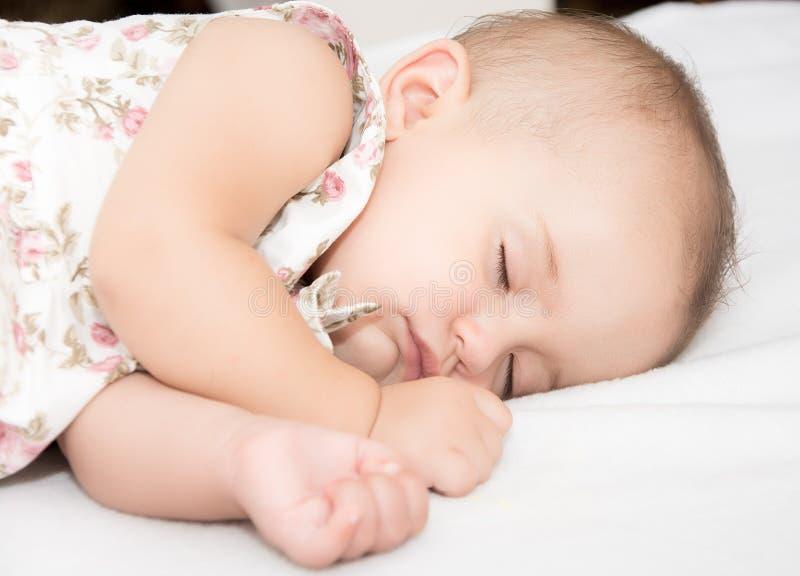 Bebé que miente en una cama mientras que duerme en un cuarto brillante fotos de archivo