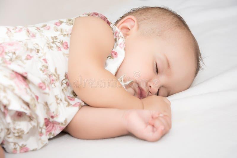 Bebé que miente en una cama mientras que duerme en un cuarto brillante foto de archivo libre de regalías