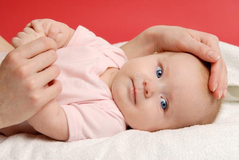 Bebé que miente en una manta blanca y su mano del ` s de la madre imagenes de archivo