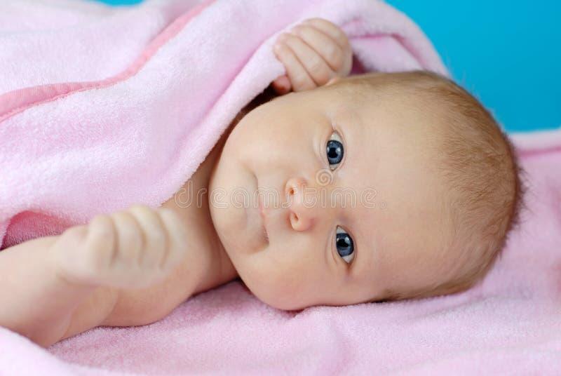 Bebé que miente en una manta rosada fotografía de archivo