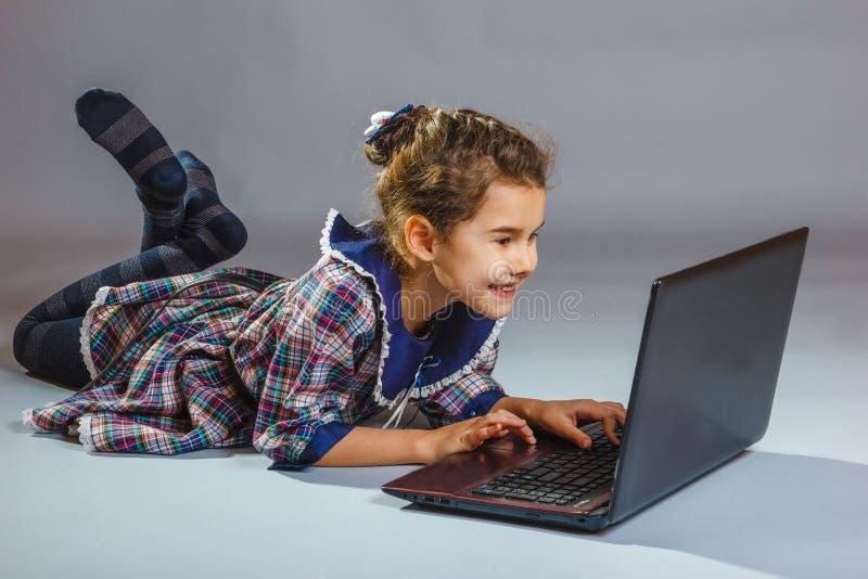 Bebé que mira el ordenador y la sonrisa foto de archivo libre de regalías