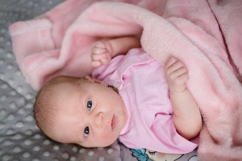 Bebé que mira en la cámara en su cama fotografía de archivo