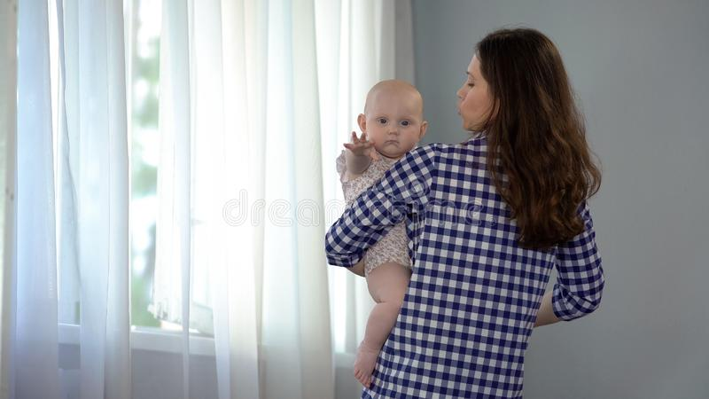 Bebé que mira en la cámara y la mano que agita, madre cariñosa que conforta al niño foto de archivo