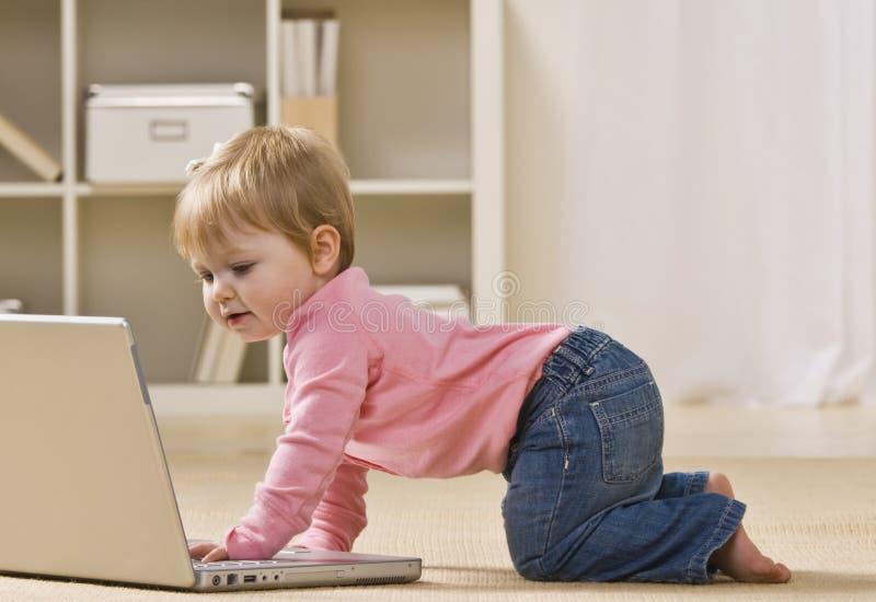 Bebé que mira la computadora portátil imagenes de archivo