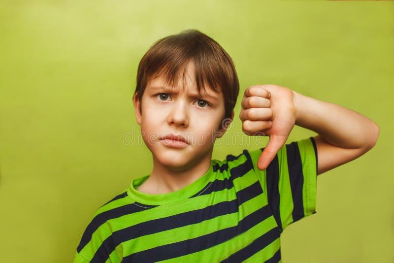 Bebé que muestra los pulgares del adolescente abajo en el grande foto de archivo