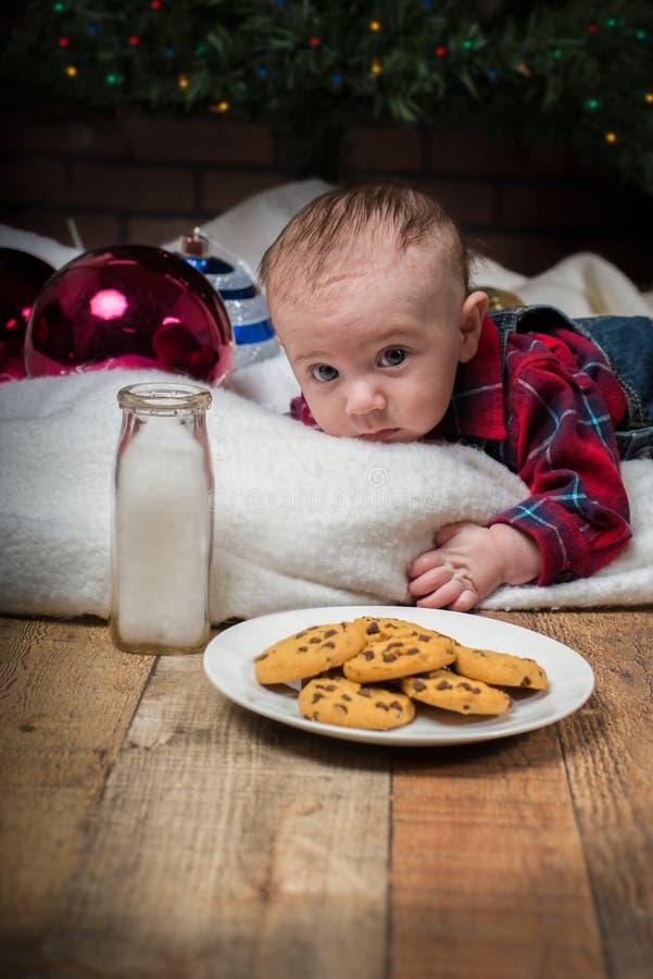 Bebé que pone debajo de árbol y que alcanza las galletas de la Navidad fotos de archivo
