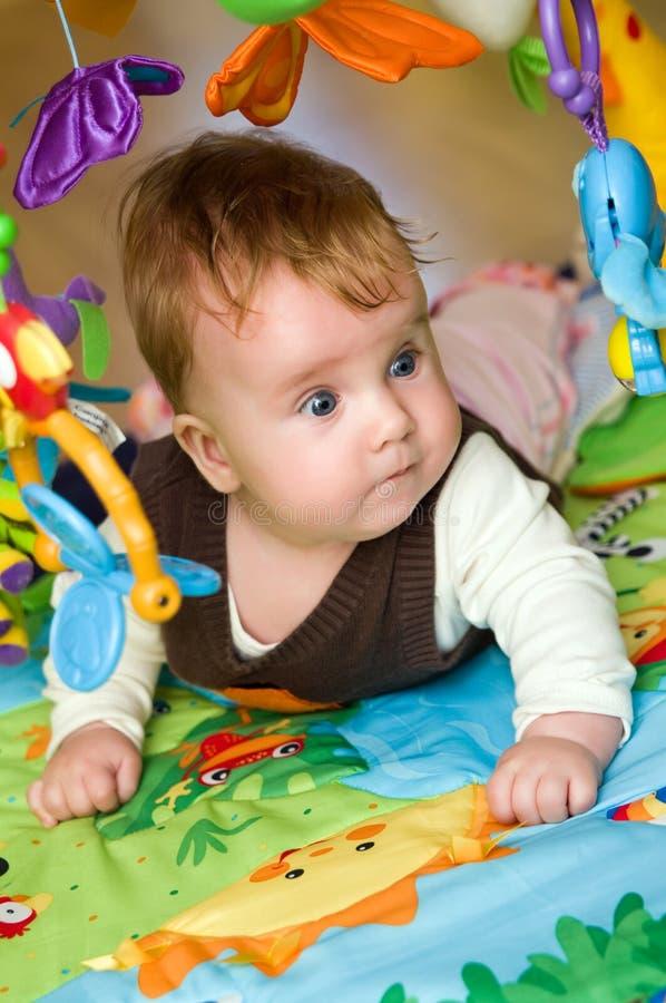 Bebé que pone en la estera colorida imagen de archivo libre de regalías