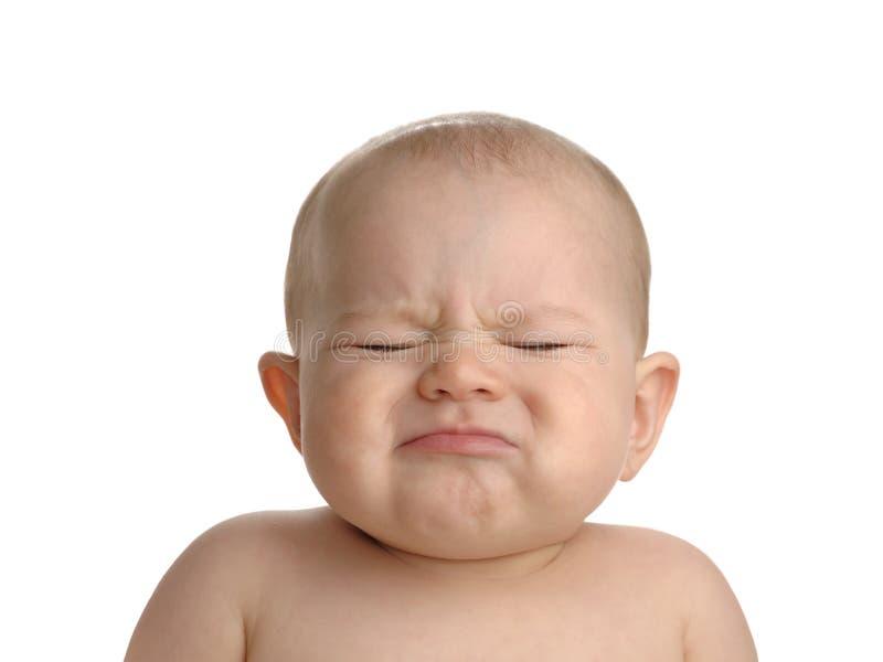 Bebé que pone mala cara aislado en blanco imagen de archivo libre de regalías