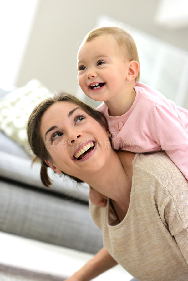 Bebé que ríe en la parte posterior de su madre fotos de archivo libres de regalías