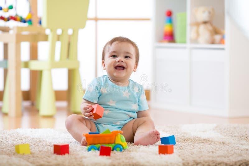 Bebé que ríe y que juega con los juguetes coloridos que se sientan en la alfombra suave en cuarto de niños imagen de archivo libre de regalías