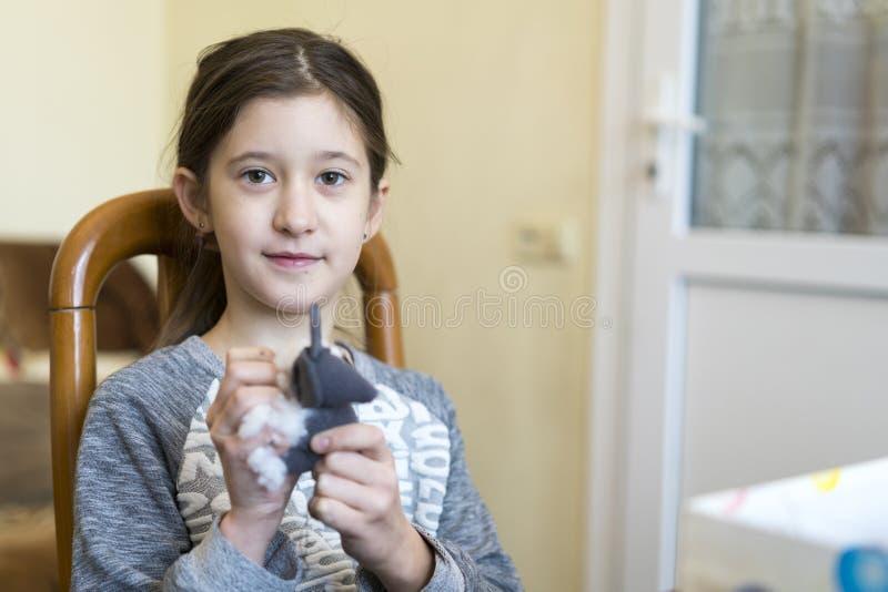 Bebé que rellena un juguete suave con algodón ig Haga a ganchillo el juguete para el niño En la tabla rosca, las agujas, gancho,  fotografía de archivo libre de regalías