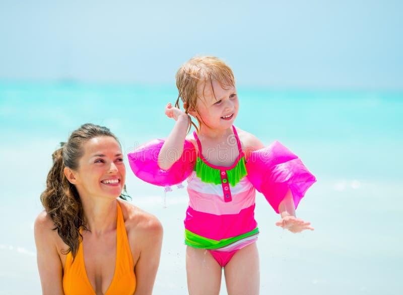 Bebé que sacude hacia fuera el agua del oído en la playa imágenes de archivo libres de regalías