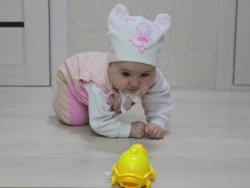 Bebé que se arrastra después de un juguete foto de archivo libre de regalías