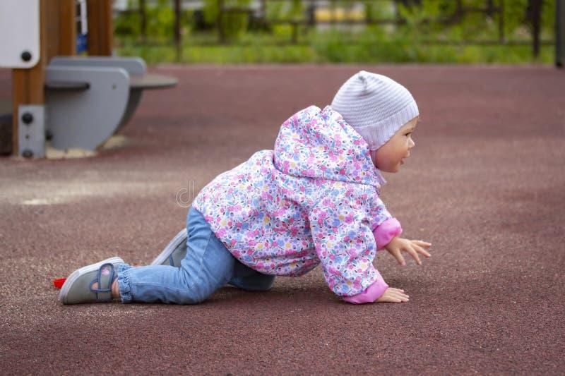 Bebé que se arrastra en el patio Un niño en ropa caliente en todos los fours Un bebé de 1 año camina cerca de la casa en primaver fotografía de archivo libre de regalías