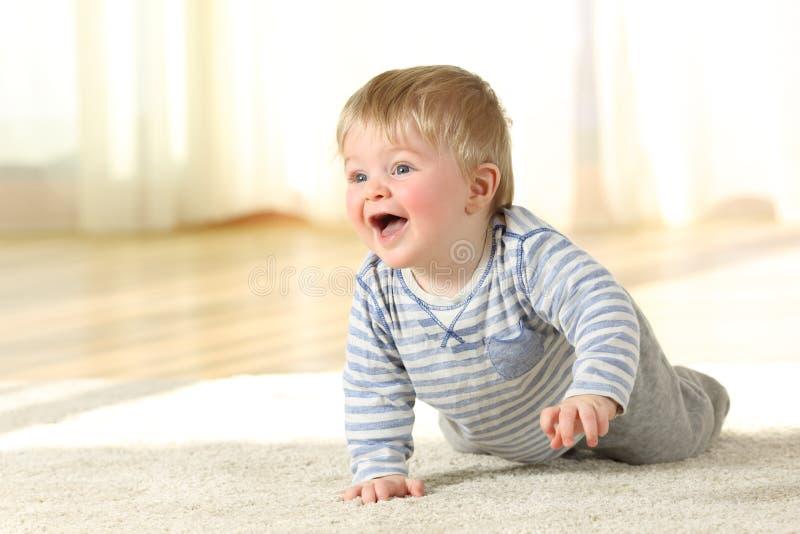 Bebé que se arrastra y que ríe en el piso en casa fotos de archivo
