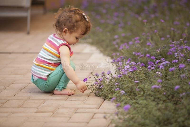 Bebé que se divierte en el jardín foto de archivo