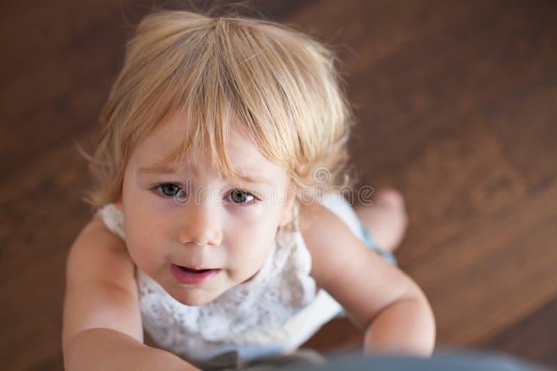 Bebé que se queja que lleva a cabo la pierna foto de archivo libre de regalías