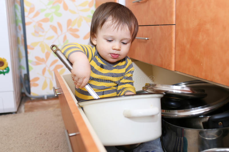 Bebé que se sienta en cajón en cocina foto de archivo libre de regalías