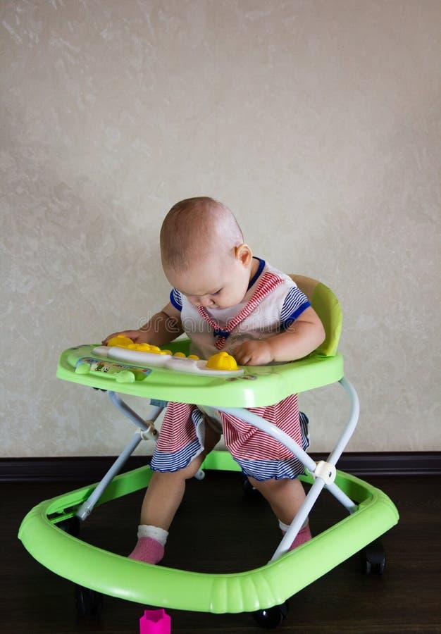 Bebé que se sienta en caminante del bebé El niño aprende caminar fotografía de archivo