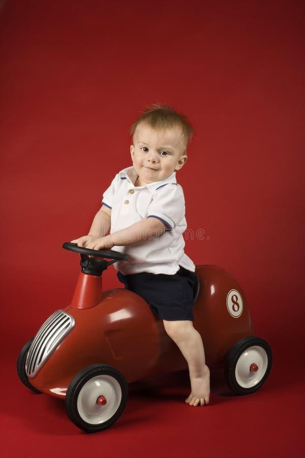 Bebé que se sienta en el coche del juego. fotos de archivo libres de regalías