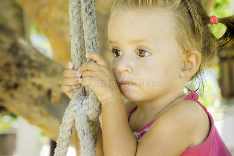Bebé que se sienta en el oscilación y que mira apagado en la distancia ella tiene ojos muy hermosos foto de archivo