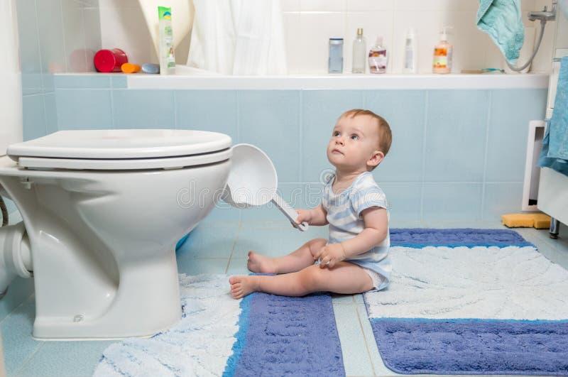 Bebé que se sienta en piso en el cuarto de baño foto de archivo