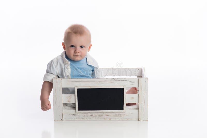 Bebé que se sienta en un cajón de la pizarra foto de archivo