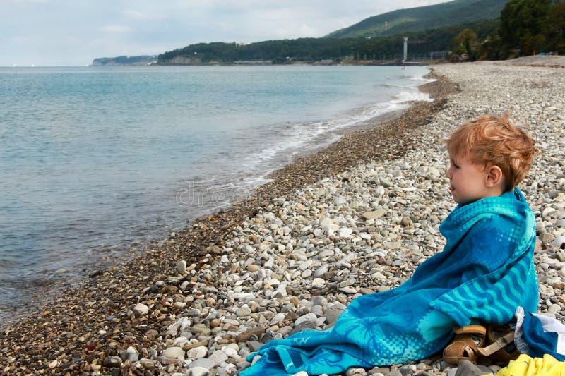 Bebé que se sienta por el mar fotografía de archivo