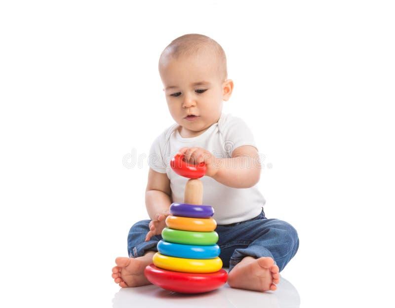 Bebé que se sostiene y que juega con los juguetes de la educación imagen de archivo libre de regalías