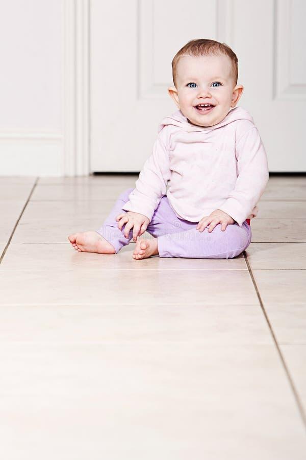 Bebé que senta-se no assoalho telhado imagem de stock royalty free