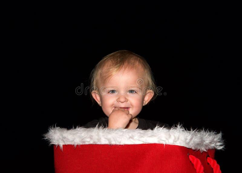 Bebé que sonríe con los fingeres en la boca que se sienta en la cesta de la Navidad que mira el espectador fotos de archivo libres de regalías