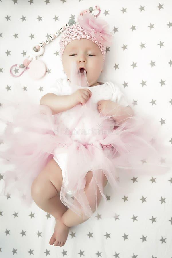 Bebé que sonríe con mejillas redondas, una falda rosada mullida y una flor en su cabeza aprendizaje recién nacido imagen de archivo