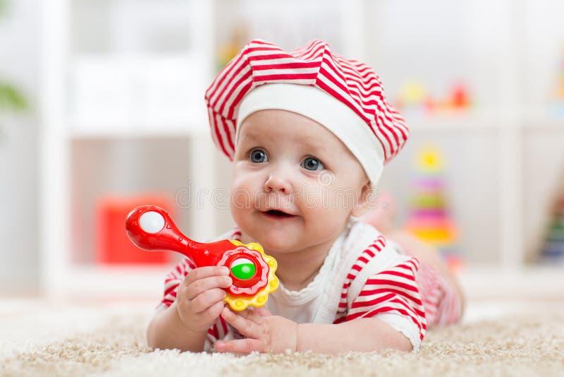 Bebé que sostiene un juguete que miente en la alfombra en sitio imagen de archivo