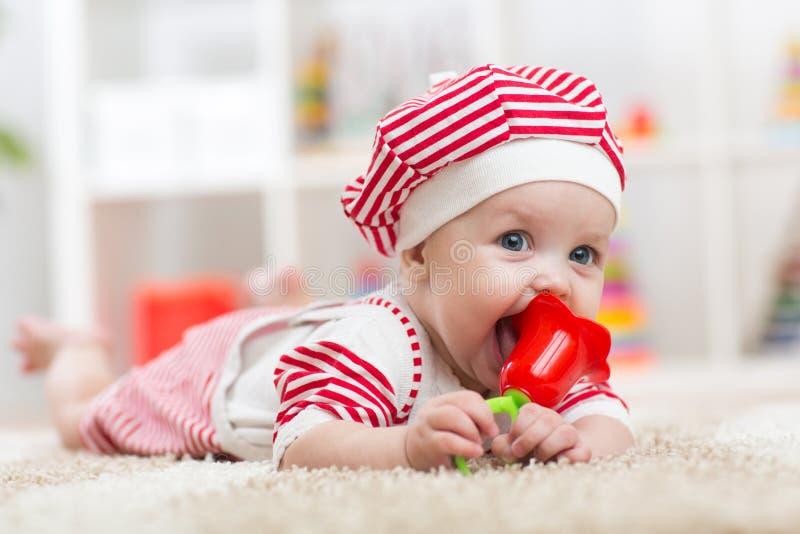 Bebé que sostiene un juguete y que miente en el vientre en el cuarto de niños imagenes de archivo