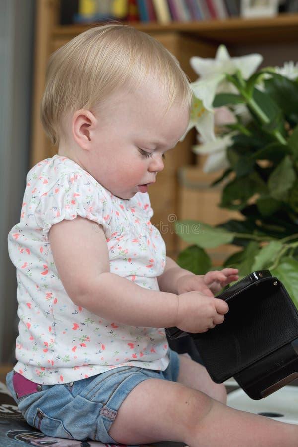 Bebé que sostiene un smartphone, sentándose en jugar de la sala de estar foto de archivo