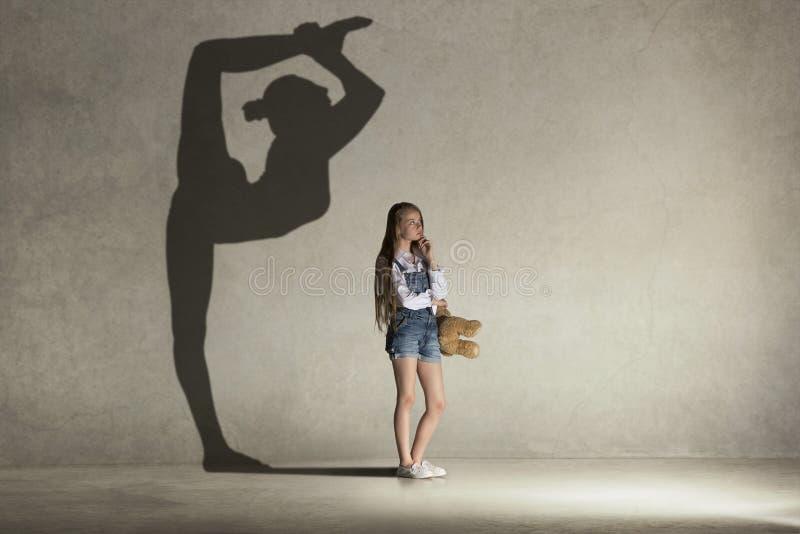 Bebé que sueña sobre la profesión del gimnasta Concepto de la niñez fotos de archivo