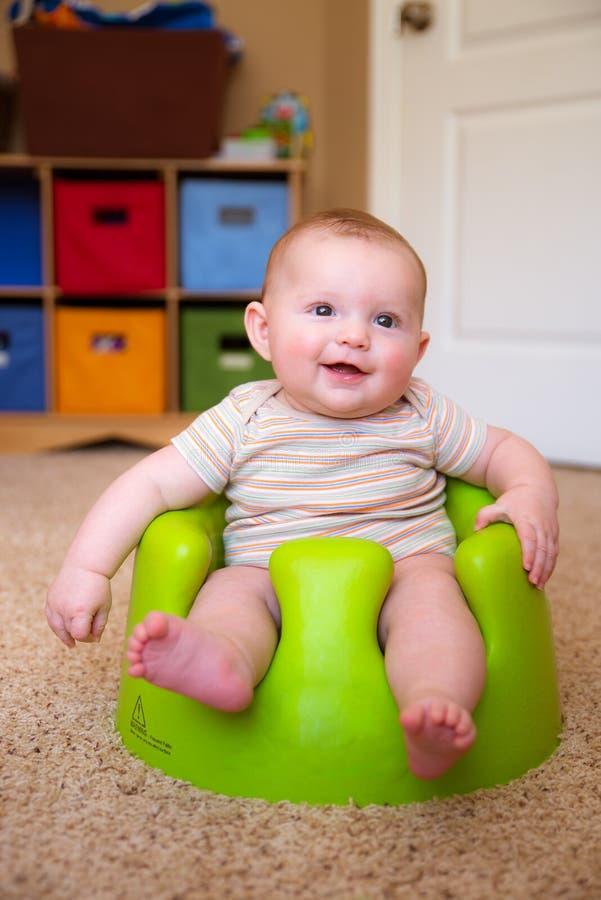 Bebé que usa el asiento de entrenamiento de Bumbo para incorporarse imágenes de archivo libres de regalías