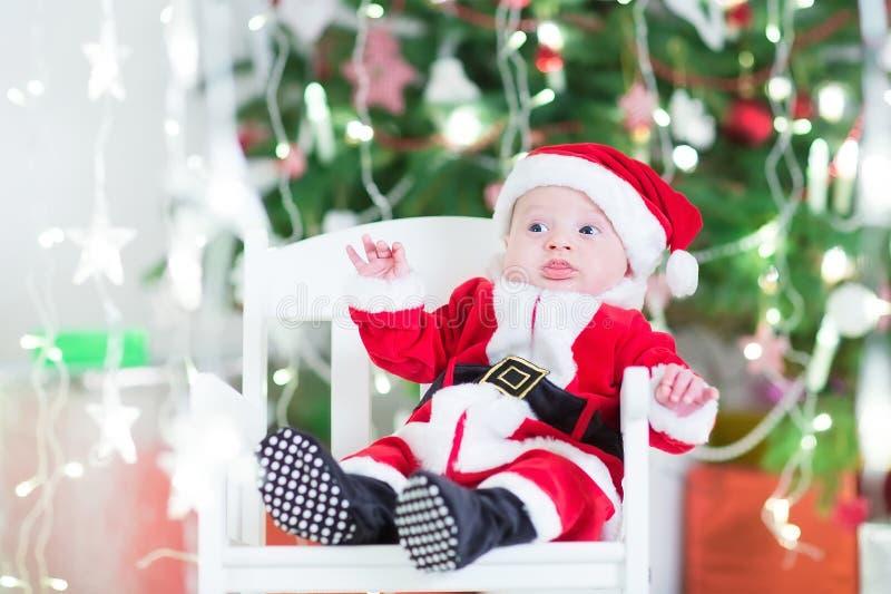 Bebé recién nacido adorable en el equipo de Sante al lado de un árbol de navidad hermoso imagenes de archivo