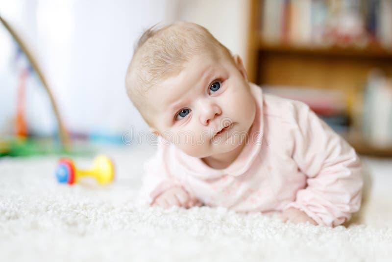 Bebé recién nacido adorable que miente en el vientre en el dormitorio o el cuarto de niños soleado blanco Materia textil y lecho  imagen de archivo libre de regalías