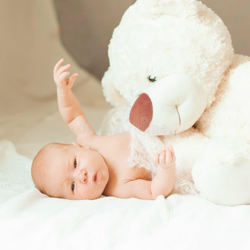 Bebé recién nacido bonito con un juguete suave grande que miente en la manta foto de archivo