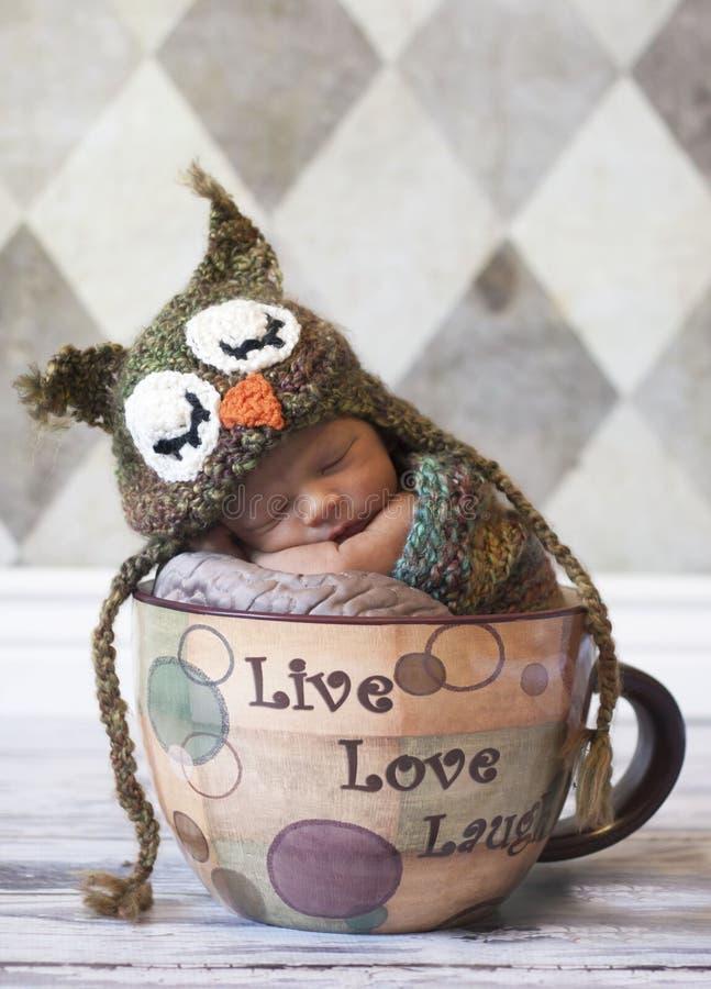 Bebé recién nacido con el sombrero del buho en taza gigante imagen de archivo