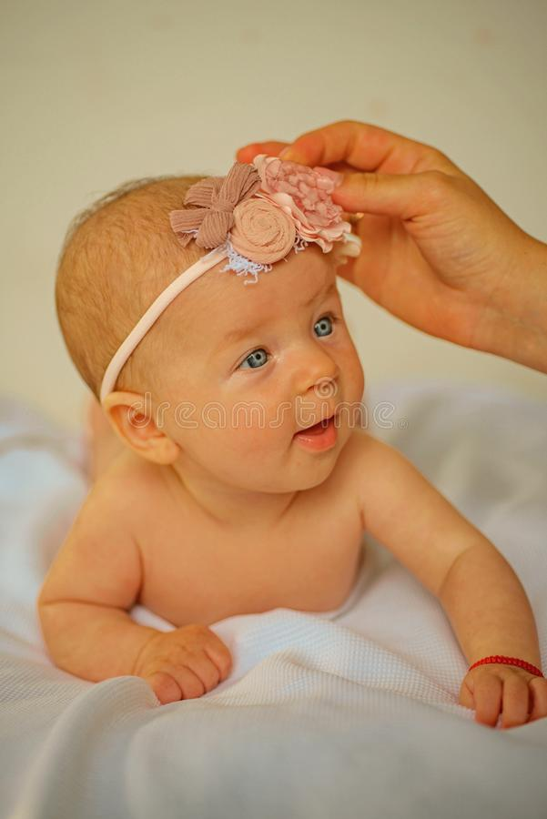Bebé recién nacido con la banda de la moda Modelo recién nacido de la muchacha de la moda Muchacha recién nacida feliz Cuidado de fotos de archivo libres de regalías