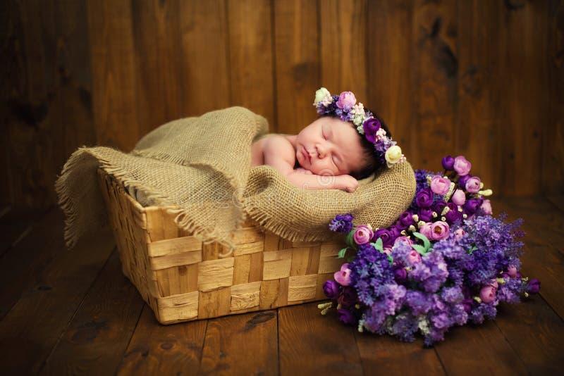 Bebé recién nacido con una guirnalda en una cesta de mimbre con un ramo de flores salvajes púrpuras foto de archivo
