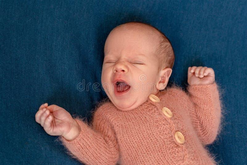 Bebé recién nacido 14 días que llevan el traje hecho punto que duerme en primer de la cama imagenes de archivo