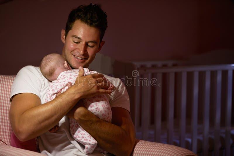 Bebé recién nacido de At Home Cuddling del padre en cuarto de niños imagen de archivo libre de regalías